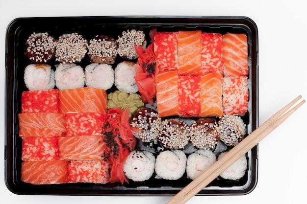 Duży zestaw sushi ib czarne plastikowe pudełko na białym, widok z góry z bliska, kopia przestrzeń