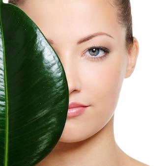 Duży zielony liść cieniujący połowę pięknej twarzy kobiety na białej przestrzeni