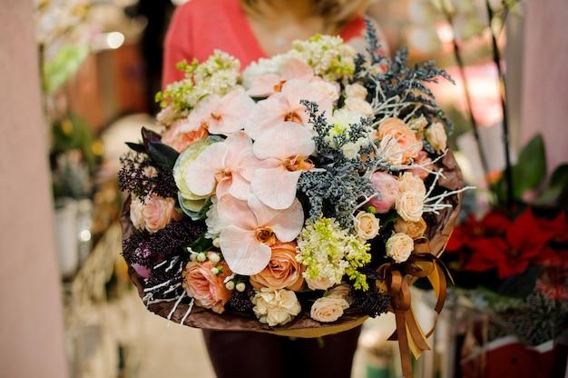 Duży zimowy bukiet kolorowych kwiatów w rękach kobiety