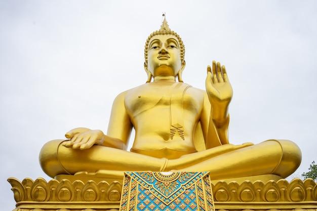 Duży złoty posąg buddy stoi wysoko i wyróżnia się