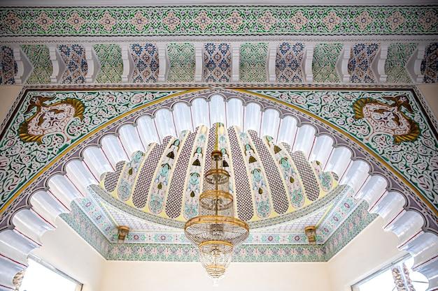 Duży złoty żyrandol na pstrokatym suficie z islamskim tradycyjnym ornamentem religijnym