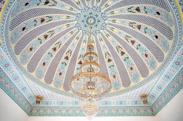 Duży złoty żyrandol na pstrokatym suficie z islamskim tradycyjnym ornamentem religijnym.