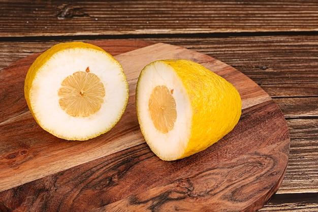Duży żółty cytron do cukierków deska do krojenia na drewnianym stole
