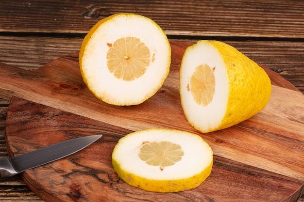 Duży żółty cytryn do cukierków deska do krojenia na drewnianym stole
