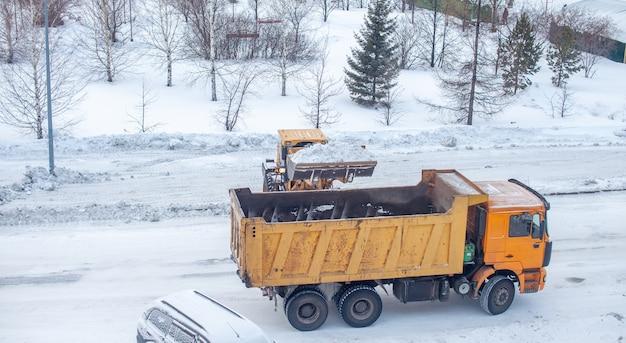 Duży żółty traktor odgarnia śnieg z drogi i ładuje go na ciężarówkę.