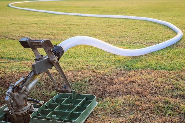 Duży zraszacz i wąż wodny w trawie stadionu piłkarskiego