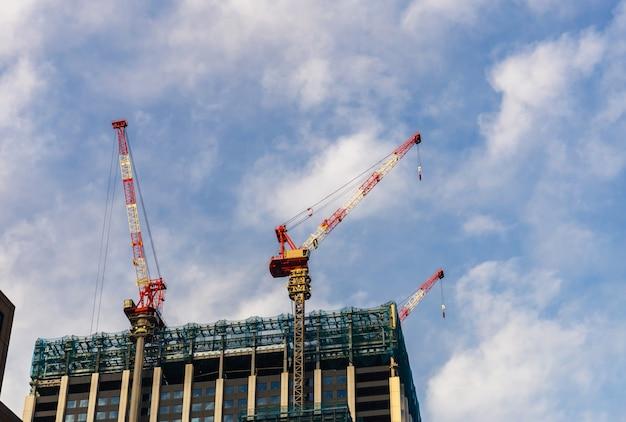 Duży żuraw i budynek budowa z niebieskim niebem