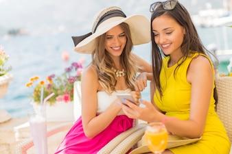 Dwa ładnej młodej kobiety bierze selfie z telefonem komórkowym morzem