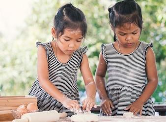 Dwa ślicznej azjatykciej małe dziecko dziewczyny przygotowywają ciasto dla wypiekowych ciastek w kuchni
