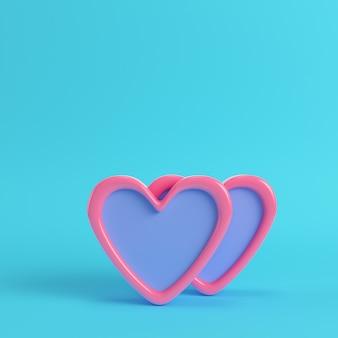 Dwa abstrakcyjne różowe serce na jasnym niebieskim tle