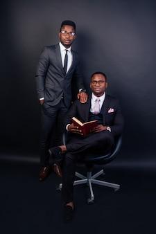 Dwa african american model biznesowy mężczyzna pozowanie na czarnym tle w studio.