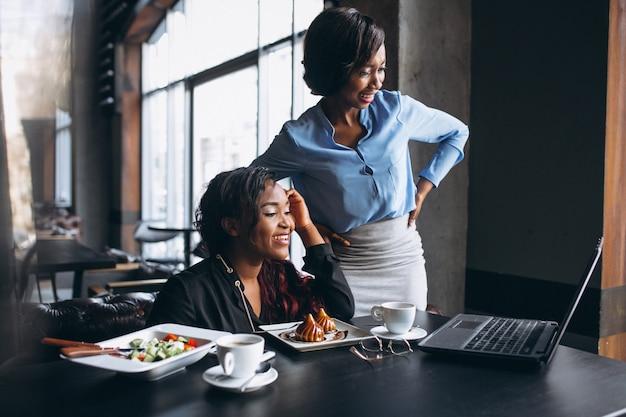 Dwa amerykanin afrykańskiego pochodzenia kobiety z laptopem i lunchem