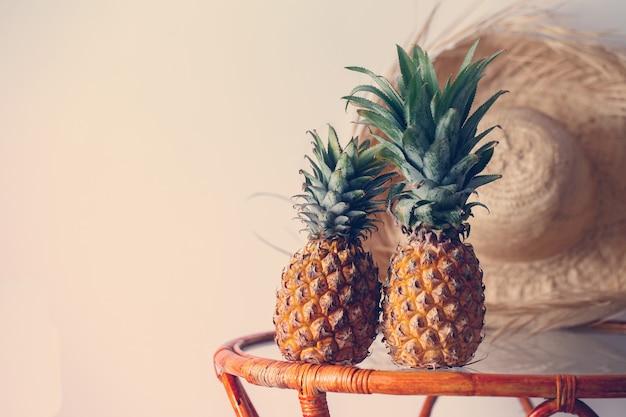 Dwa ananasy na szklanym stole na jasnym tle