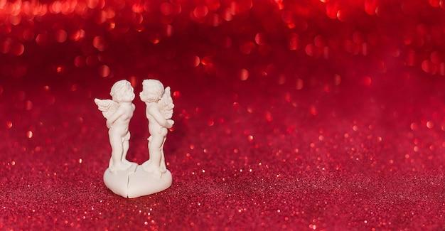 Dwa anioły całuje na czerwonym tle z bokeh walentynki amorek, kopia przestrzeń