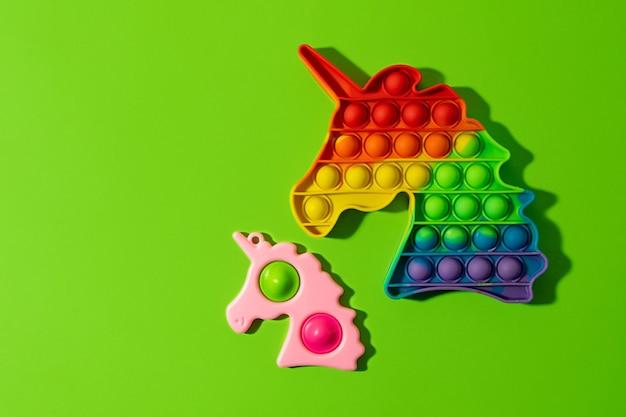 Dwa antystresowe fidgety strzelają i prostym dołeczkiem na zielonym tlenowa sensoryczna zabawka antystresowa