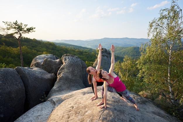 Dwa atrakcyjnej szczupłej kobiety robi skomplikowanej joga pozie dalej zaświecającą lato ranku słońca wierzchołkiem ogromna skała na jasnym niebieskiego nieba tle