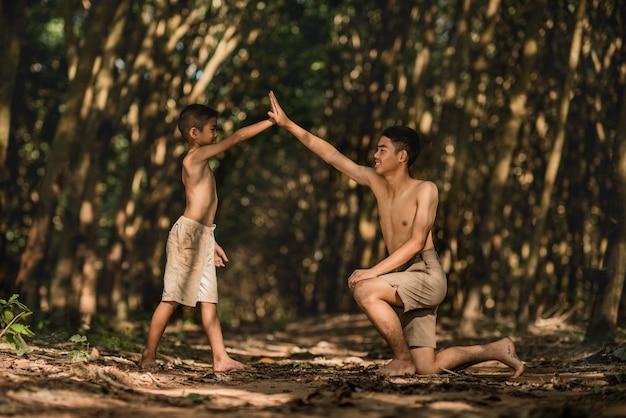 Dwa azjata chłopiec ściska rękę na natury blackground, kraj