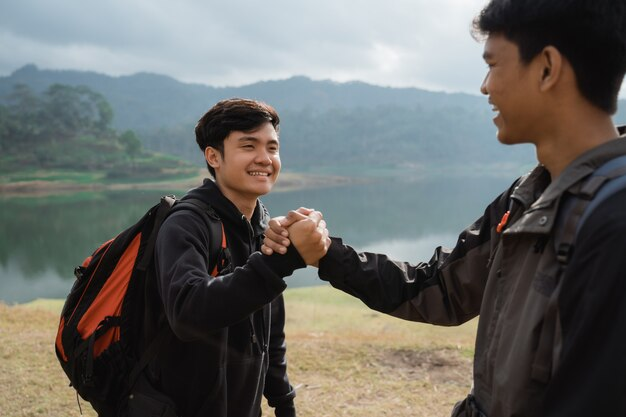 Dwa azjata z przyjaźni ręką stoi blisko jeziora