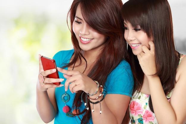 Dwa azjatyckich kobiet tekst na jej telefonie komórkowym