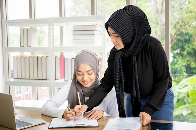 Dwa azjatyckich muzułmańskich bizneswomanów opowiada wpólnie i pracuje w biurze