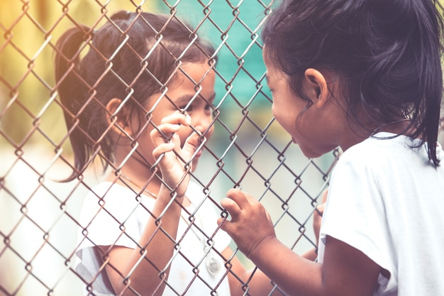 Dwa azjatyckie dzieci rozmawiają ze sobą i ręka trzyma stalową siatkę w tonie vintage kolor