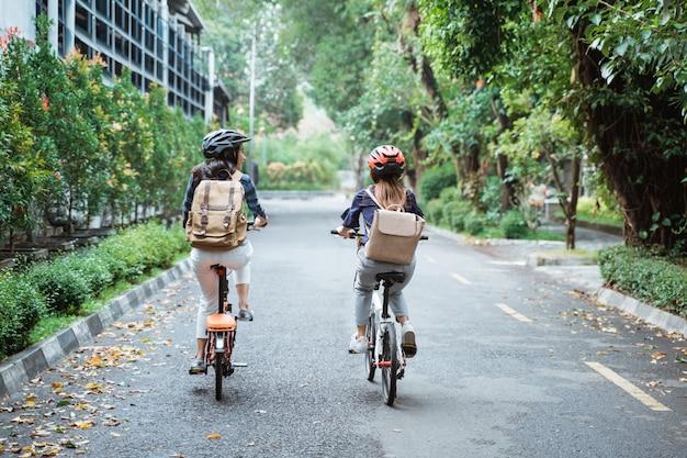 Dwa azjatykcia kobieta jest ubranym hełm i niesie torby jedzie rower