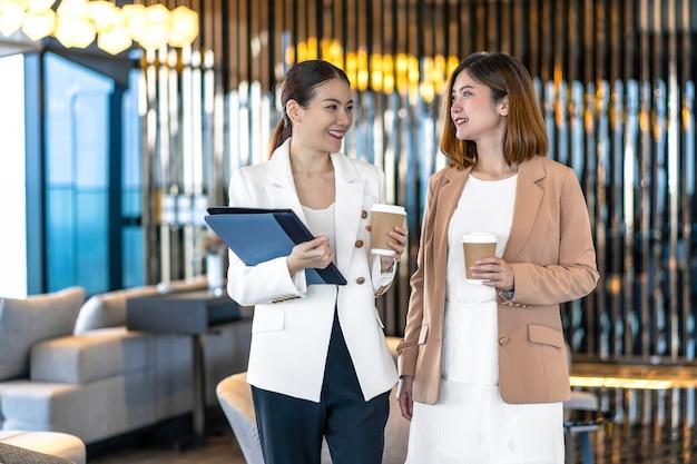 Dwa azjatykciego bizneswomanu opowiada podczas kawowej przerwy w nowożytnym biurze lub coworking przestrzeni