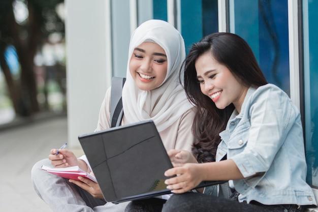 Dwa azjatykciego studenta collegu używa laptop