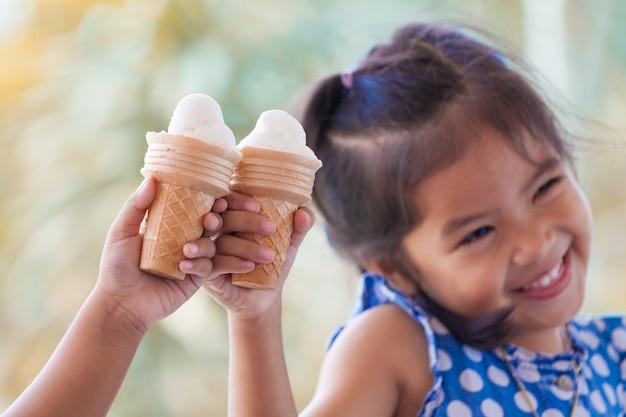 Dwa azjatykciej małej dziewczynki trzyma roztapiającego lody gofra konusują wpólnie w rocznika koloru brzmieniu