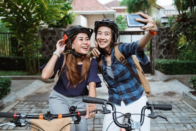 Dwa azjatykciej młodej kobiety jest ubranym hełm i torby z kamera telefonem komórkowym robią wideo na falcowanie rowerze