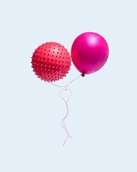 Dwa balony z linami, które tworzą serce na białym tle na niebieskim tle. pojęcie walentynek i miłości. pionowy układ prostokąta. minimalny.
