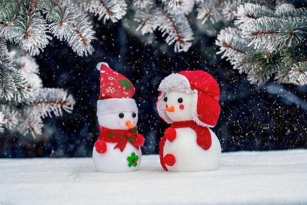 Dwa bałwanki zabawki pod świerkiem na ciemnym tle w zimie podczas opadów śniegu. kartka z życzeniami świątecznymi i noworocznymi