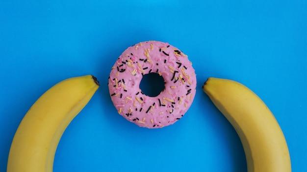 Dwa banany i różowy pączek na niebieskim tle. koncepcja erotyczna
