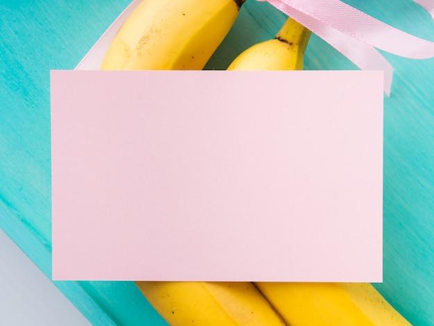 Dwa banany z różową wstążką i kartką na zielonym pastelu