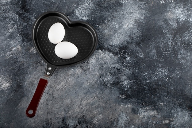 Dwa białe jajka na patelni w kształcie serca.