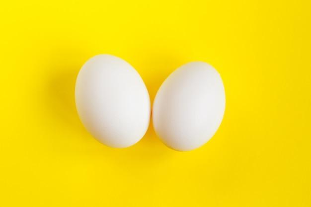 Dwa białe jajka na żółtym. kreatywna koncepcja w stylu minimalizmu