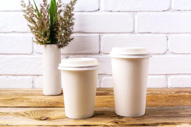 Dwa białe kubki do kawy jednorazowe z makietą przykrywki z trawą kordową i zielonymi liśćmi