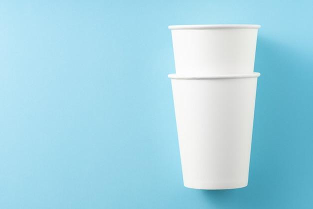 Dwa białe papierowe kubki na niebieskim tle. widok z góry. miejsce na tekst. koncepcja ekologii.