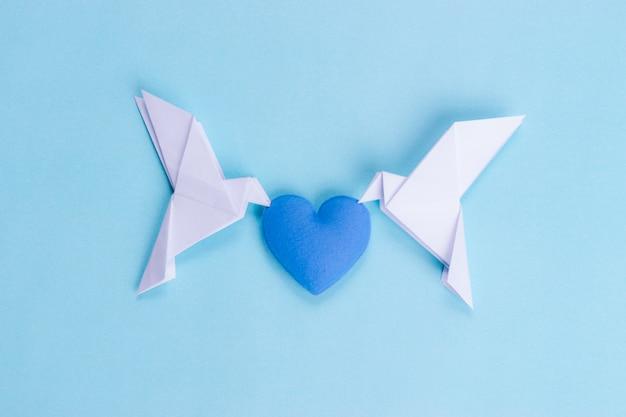 Dwa białe ptaki wykonane z papieru niosącego niebieskie serce. międzynarodowy dzień pokoju.