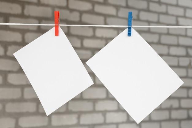 Dwa białe puste kartki notatek z bielizny wiszące na tle cegieł