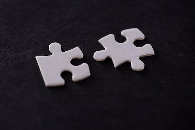 Dwa białe puzzle na białym na czarnym tle.