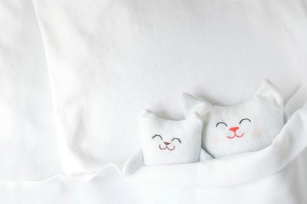 Dwa białe ręcznie robione koty śpią na białym łóżku.