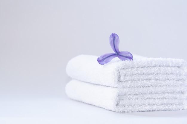 Dwa białe, starannie złożone ręczniki frotte z kwiatem fioletowej irysa