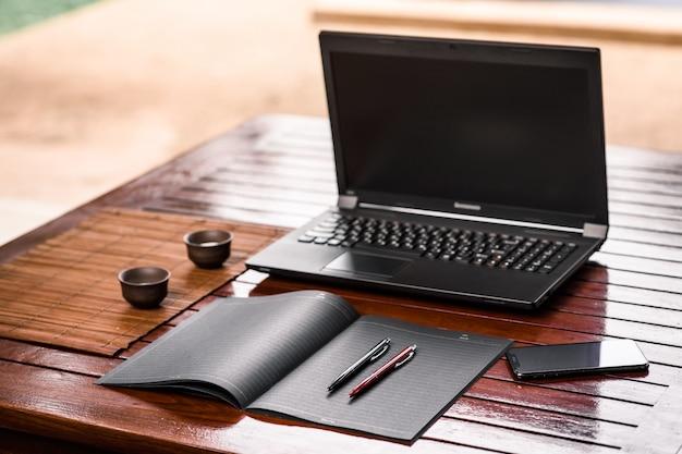 Dwa biurowe długopisy w kolorze czarnym i czerwonym umieszczone na czarnym zeszycie leżącym na drewnianym stole, na którym stoi otwarty laptop, czarny telefon i dwie filiżanki do napojów