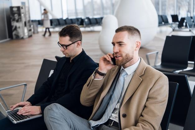 Dwa biznesmena pracuje na laptopie przy lotniskiem
