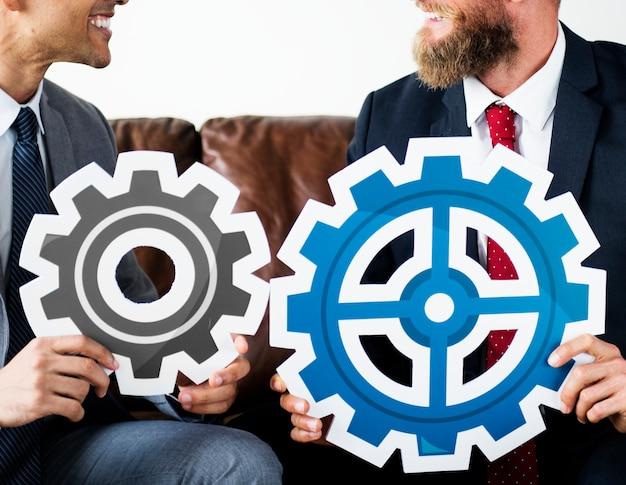 Dwa biznesmenów obsiadanie na leżanki przewożenia przekładni ikonach