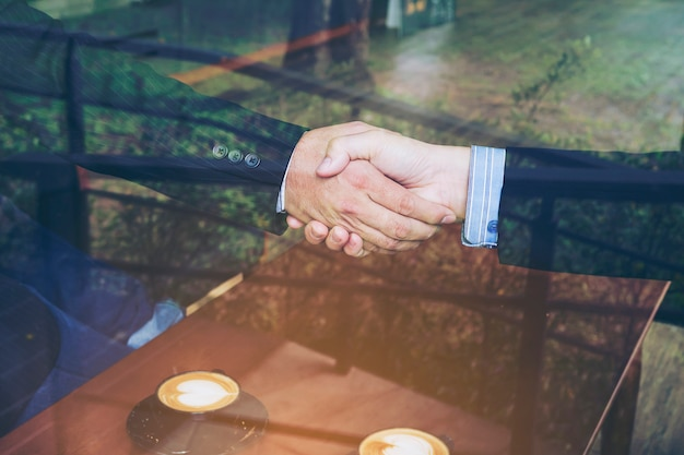 Dwa biznesmenów potrząśnięcia ręka w sklep z kawą