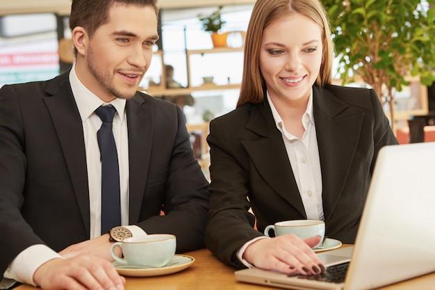 Dwa biznesowego kolegi używa laptop przy kawiarnią