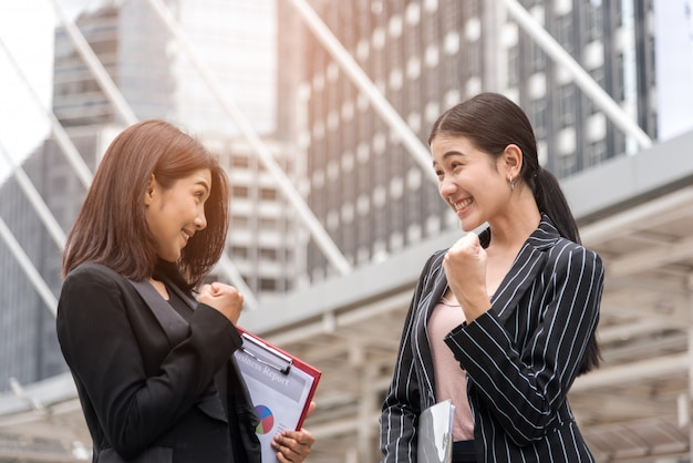 Dwa biznesowej kobiety ręki podwyżki szczęśliwy przy plenerowym, biznesowym acheive i pomyślnym pojęciem