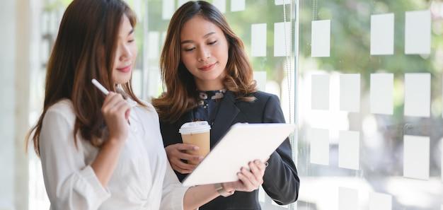 Dwa bizneswomanów dyskutuje plan biznesowego wpólnie w nowożytnym workspace